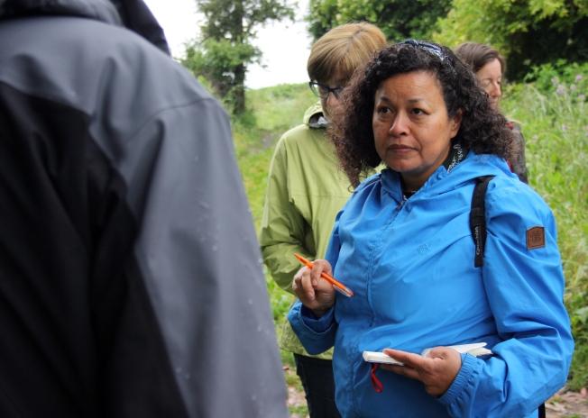 Marlene Anaya escoita o que conta o biólogo César López durante a camiñada